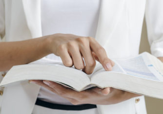 closeup of woman's hands skimming through a dictionary