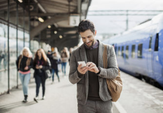 Photo of a smiling businessman texting on his mobile phone at train station